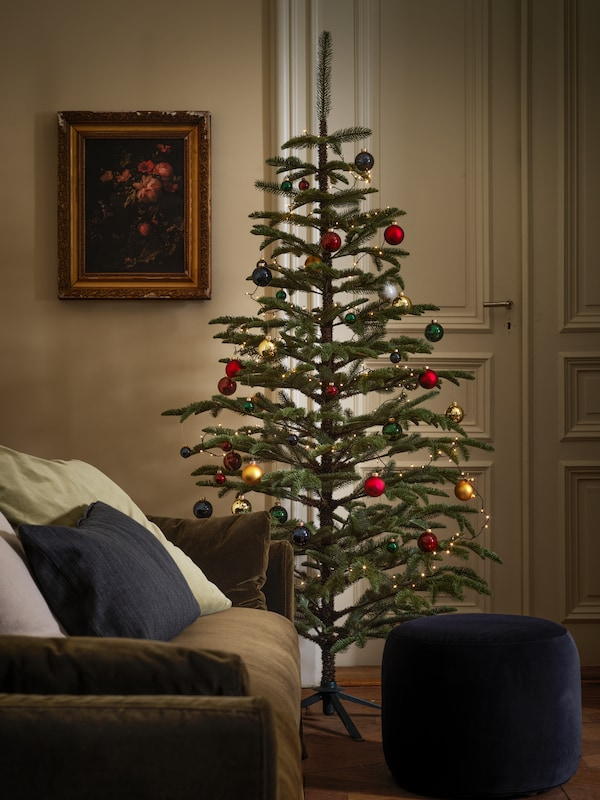A large Christmas tree stands in a traditional-looking living room, its branches decorated with bright-coloured baubles.