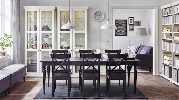 A Large Dining Room With An Extendable Table And Chairs In Black White Gl