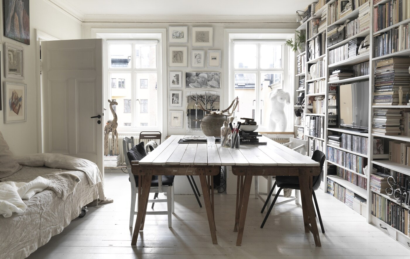 A large dining table and wall of bookshelves.