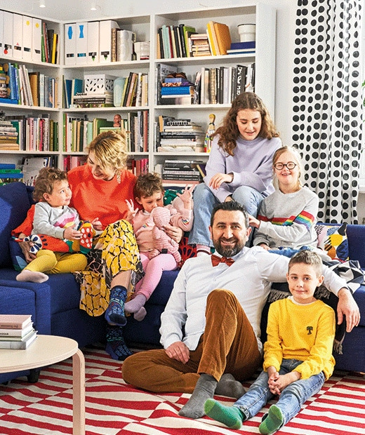 A large family – parents and children – gathered in and around a blue sofa; striped rug in front, filled bookcases behind.