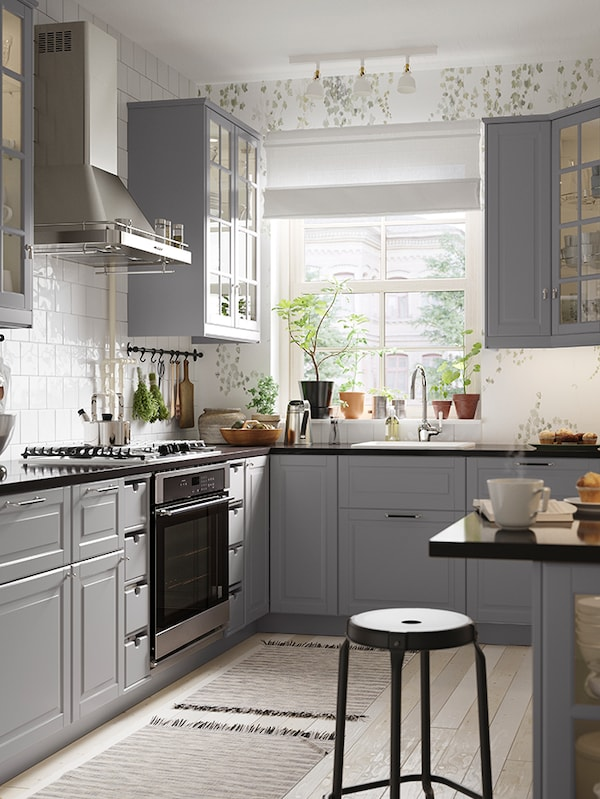 A large gray kitchen with stainlesss teel appliances
