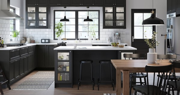 A large kitchen with dark wood fronts, two black ceiling lamps hanging over the sink, and two large windows against the wall.