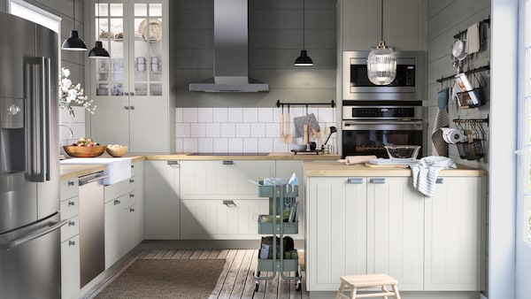A large kitchen with green and white walls, a kitchen island with bakeware, black rails with hooks, a trolley.