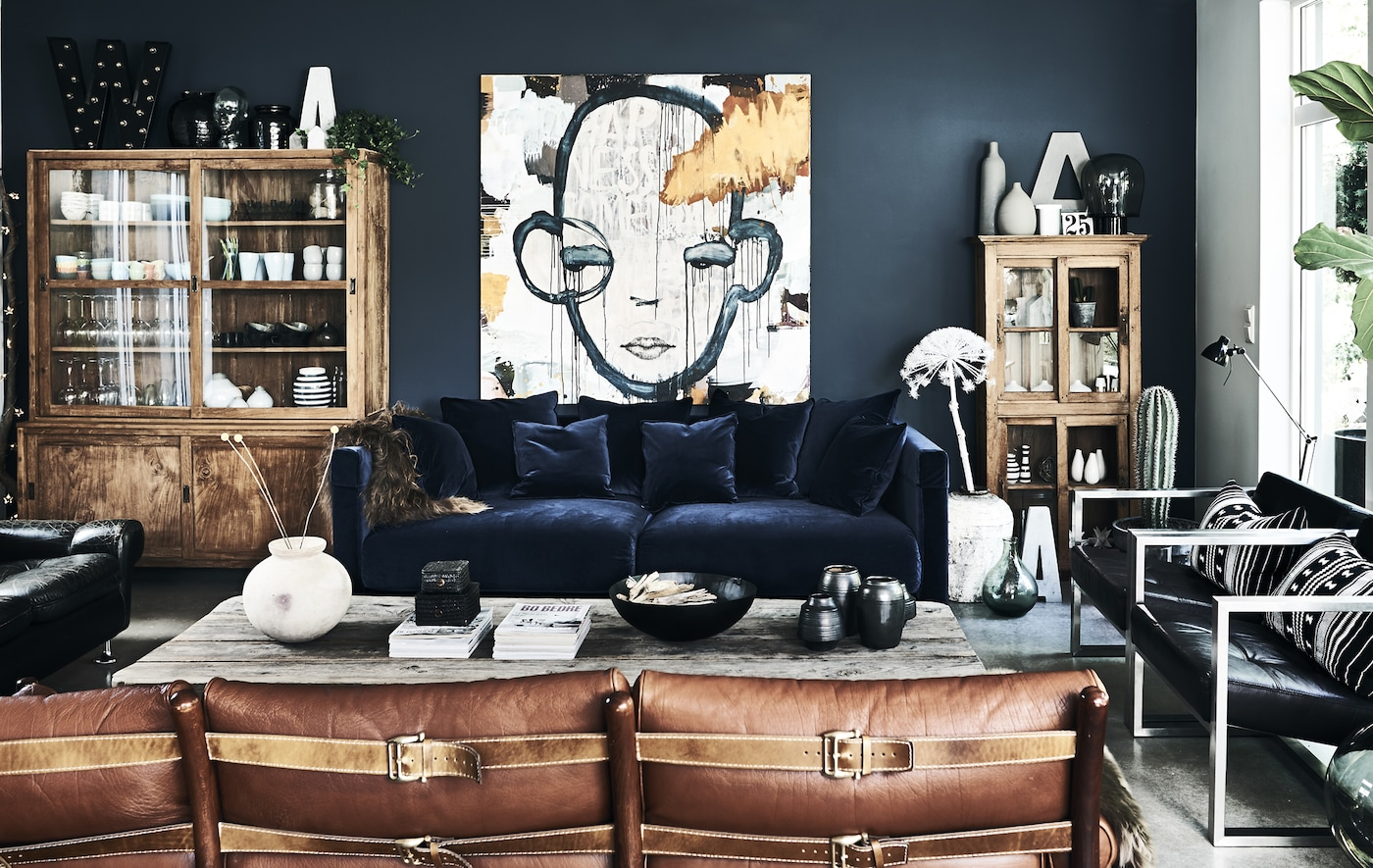 A large living room featuring blue velvet sofa, brown leather sofa and black leather armchairs, all facing a grey wood table.