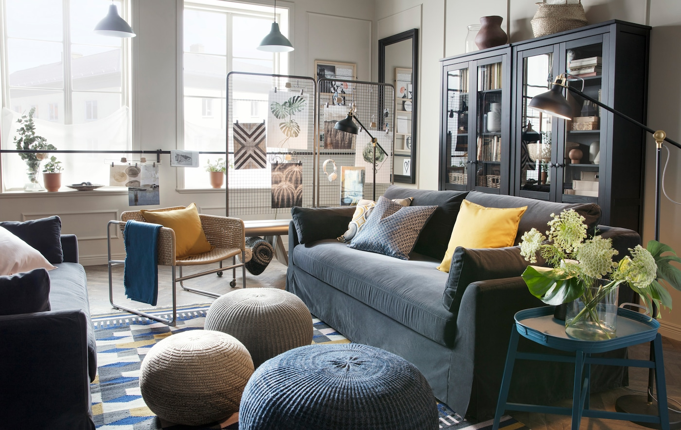 A large living room with two blue sofas facing each other, armchairs, footstools and large display cabinet.