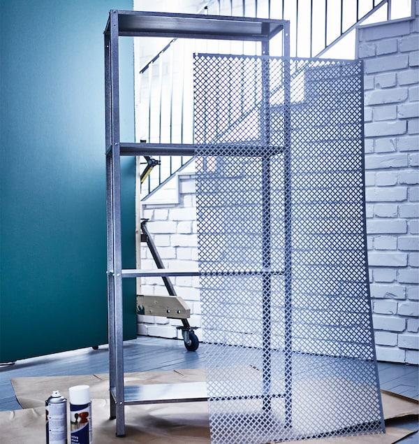 A large mesh metal sheet leans against an unpainted IKEA HYLLIS shelving unit.