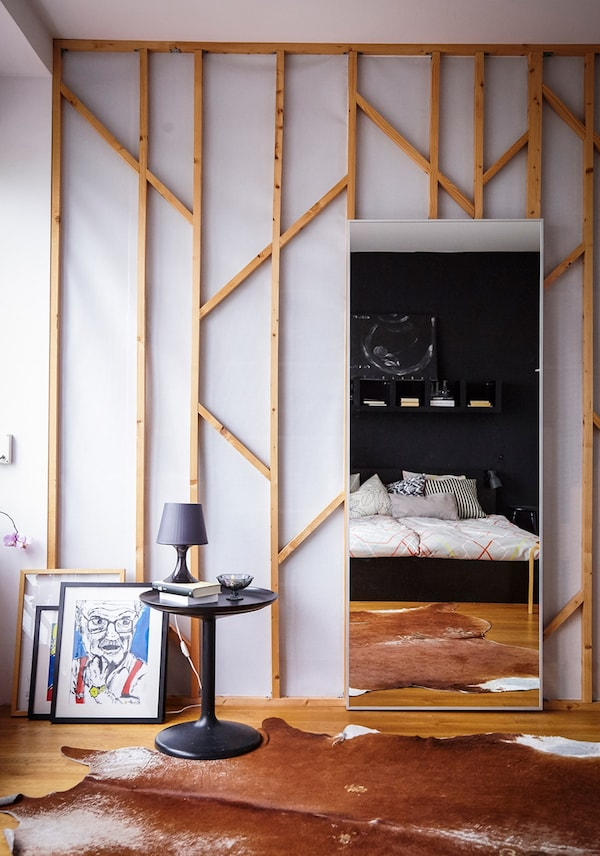 A large mirror leaning on a wall in a bedroom.