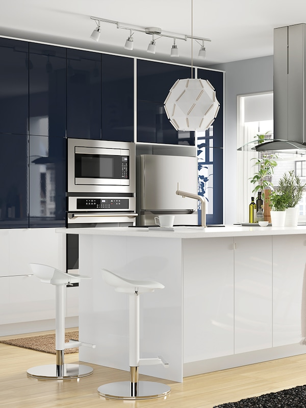 A large modern kitchen with blue and white cabinets