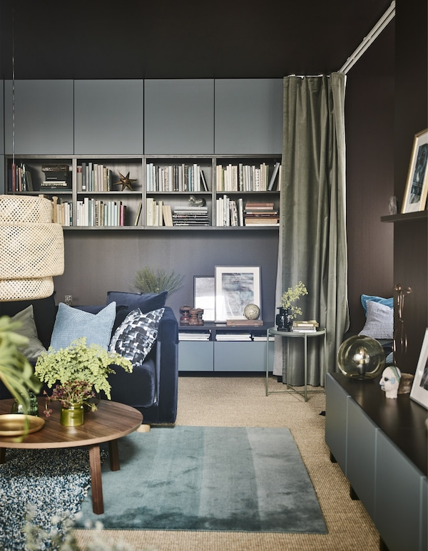 A large modern living room with dark brown walls and turquoise furnishings.