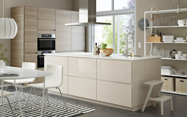 A large open plan kitchen and dining room in whites, light beige, and walnut features a high-gloss island with sink.