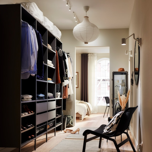 A large, open wardrobe solution in dark grey with folded clothes on shelves, hanging clothes on rails and four drawers.