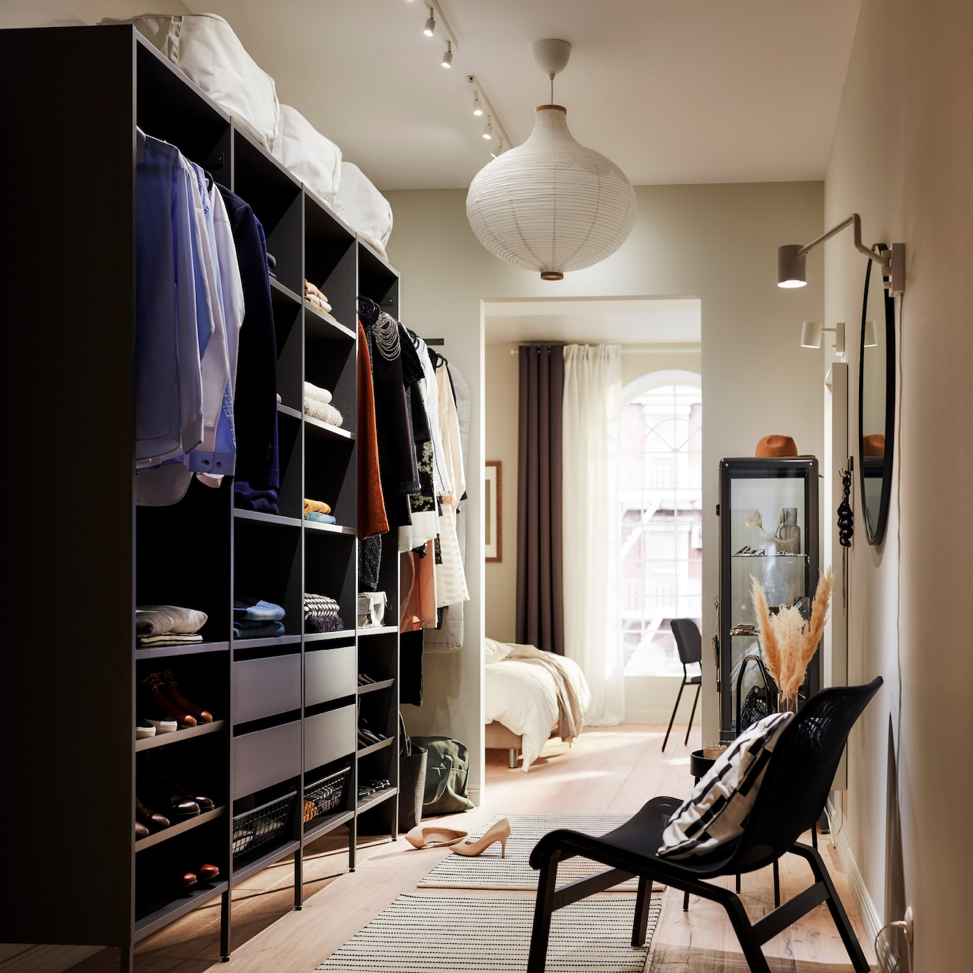 A large, open wardrobe solution with folded clothes on shelves, hanging clothes on rails, and four drawers.