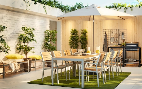 A large outdoor dining area by a white brick wall and light wood wall. Two SJÄLLAND tables sit under a beige parasol.