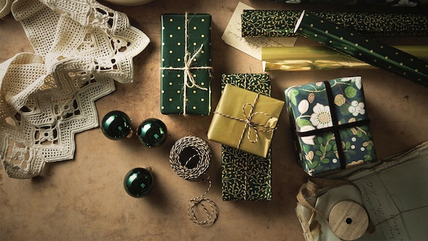 A large selection of gifts in traditional IKEA VINTER 2020 wrapping paper, twine used to wrap them.