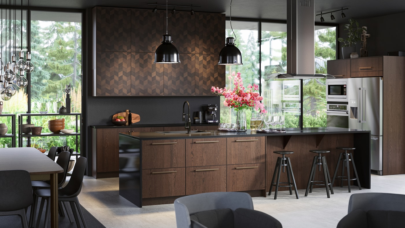 A large stylish kitchen island with wooden fronts. Black bar stools, black pendant lamps, a ceiling-mounted extractor.
