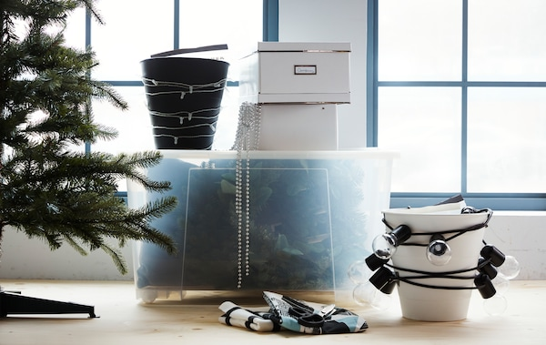 A large transparent storage box and two bins with lighting chains wrapped around them.