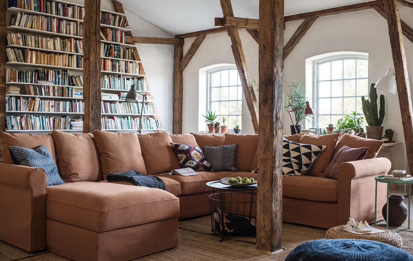 A large U-shaped sofa in a room with exposed beams.
