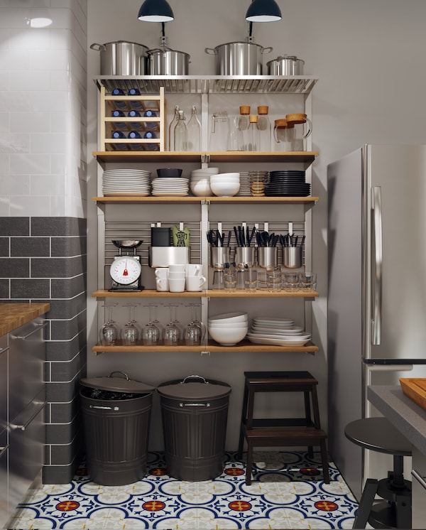 A large wall-mounted storage solution with wooden shelves, containers, rails grids and more and it holds many kitchen items.