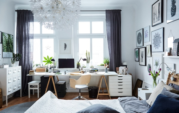 A large white bedroom with a home office space set in front of large windows.