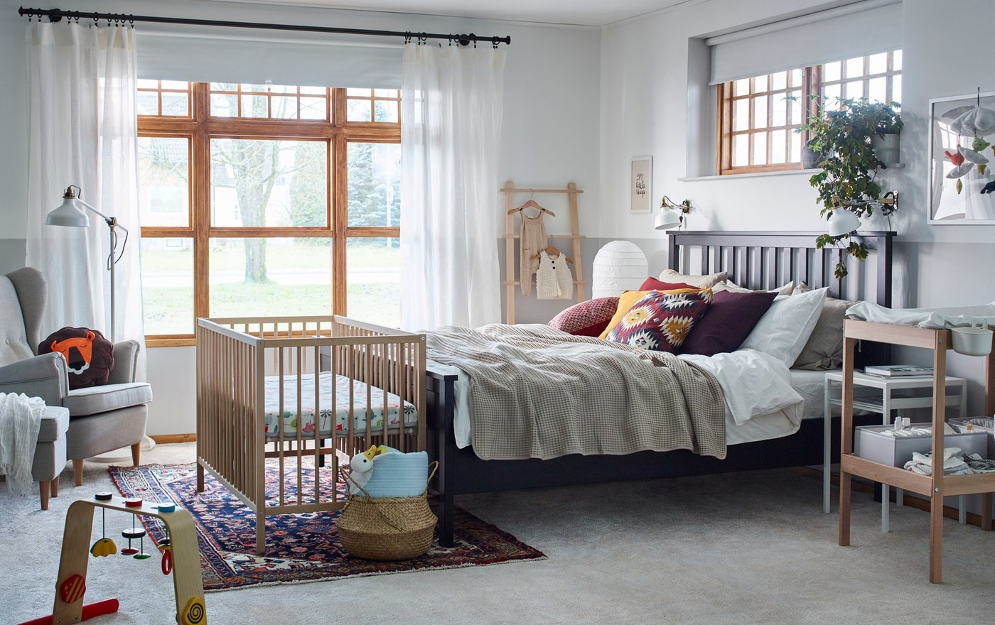 A large white bedroom with wood accents is furnished for a couple and their baby, including a SNIGLAR cot.