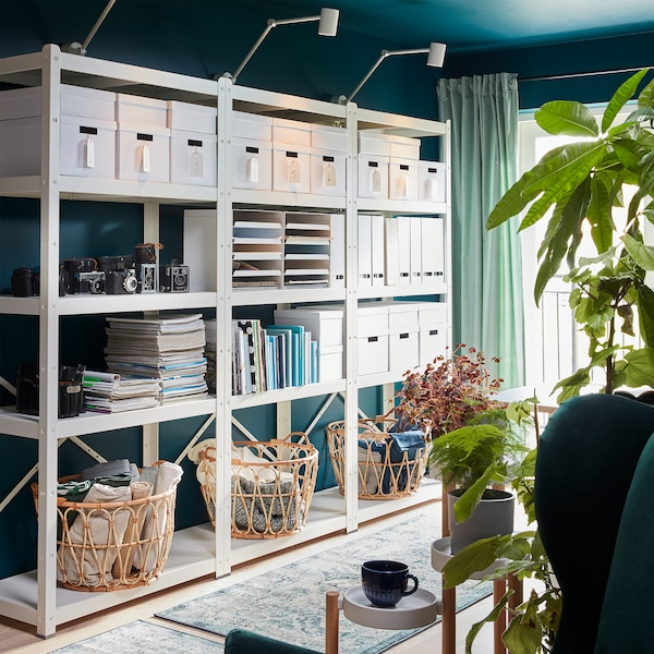 A large white BROR shelving unit with storage boxes, cameras, magazines, books, magazine files and three baskets in rattan.