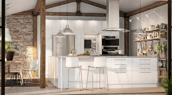 A large white kitchen featuring stainless steel appliances.