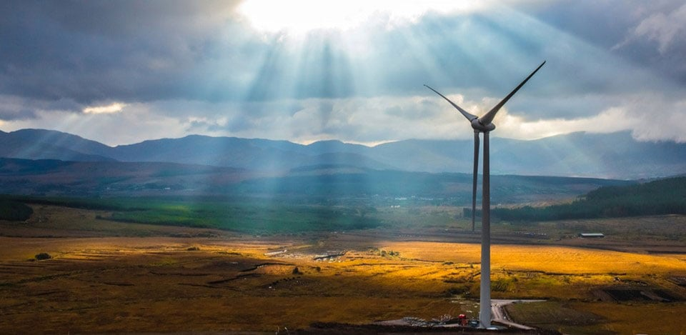 A large wind turbine in a field with mountains in the background and sunshine beaming down from the clouds.