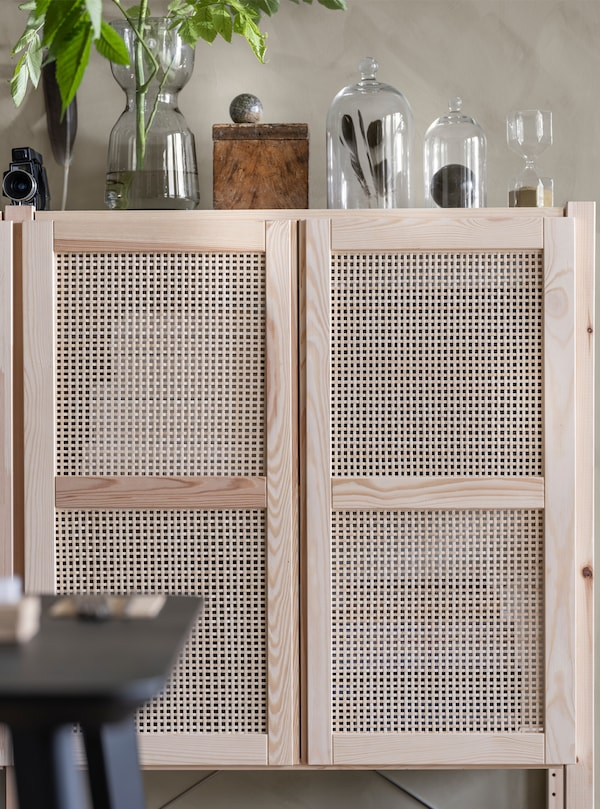 A lattice-fronted wall cupboard with glass vases on top with plant, feathers and other accessories in them.
