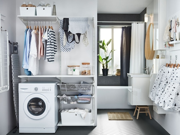 A laundry area in a bathroom with deep mesh shelves, hanging rails for drying laundry and KUGGIS plastic boxes.