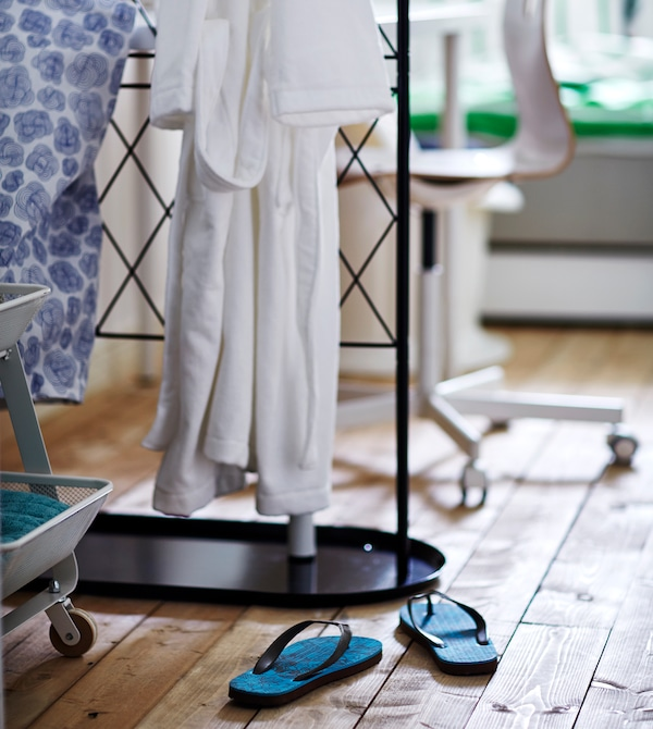 A laundry bag and bathrobe hang from a black trellis, flip flops sit on the floor below.