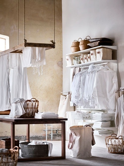 A laundry room with a brown wooden table in the centre and a BOAXEL system mounted on the white wall.