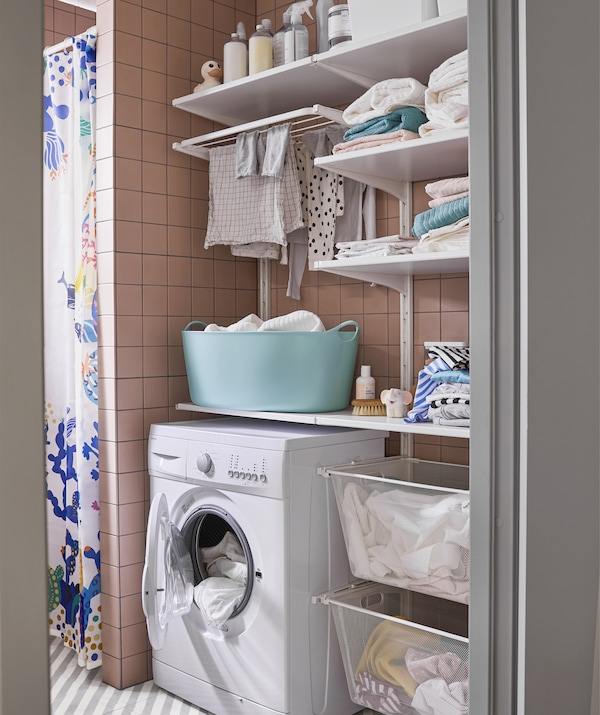 A laundry space with washing machine, shelves and baskets.