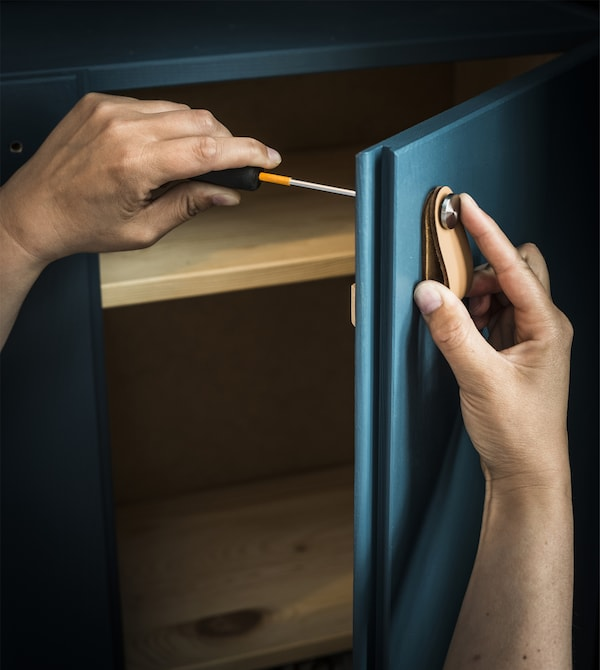 A leather handle being screwed into a custom painted IVAR cabinet.