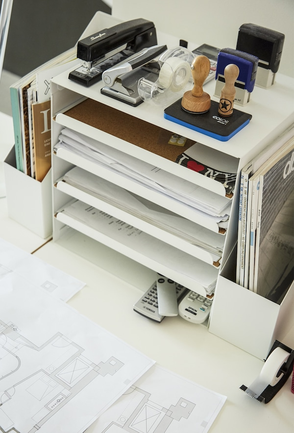 A letter tray and stationery on a desk.
