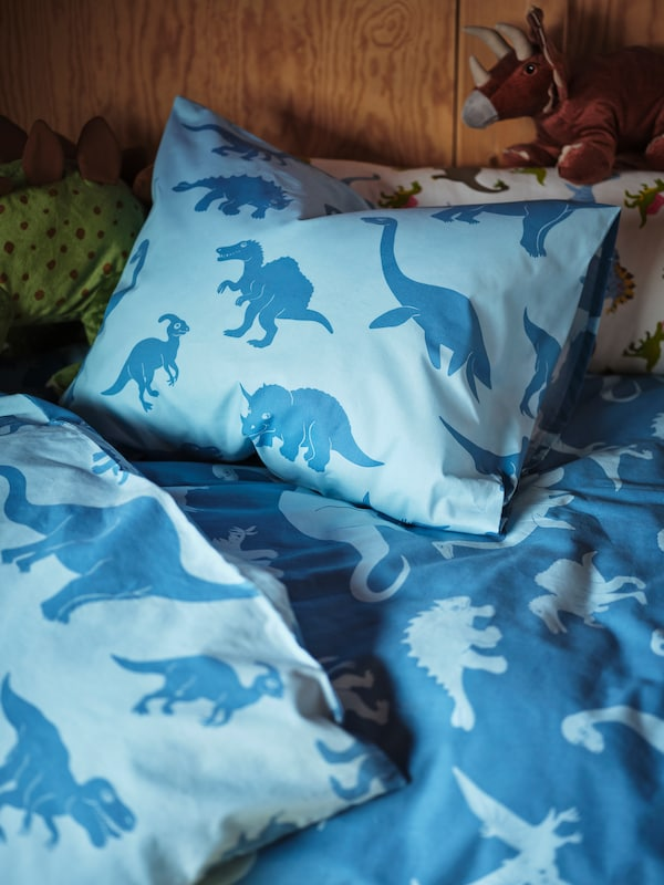 A light and dark blue dinosaur quilt and pillow sit on a child's bed, while two JÄTTELIK dinosaurs peek out.