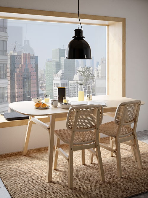 A light bamboo dining table by a large window with a city view, two light bamboo chairs and breakfast on the table.