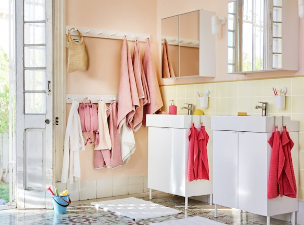 A light bathroom setting with various towels in both pink and coral, and bags hanging on the wall.