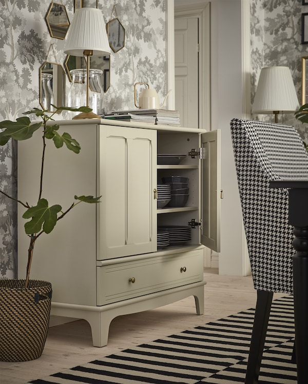 A light beige cabinet with an open door, dark grey dinnerware is stored inside and a table lamp in brass/white stands on top.
