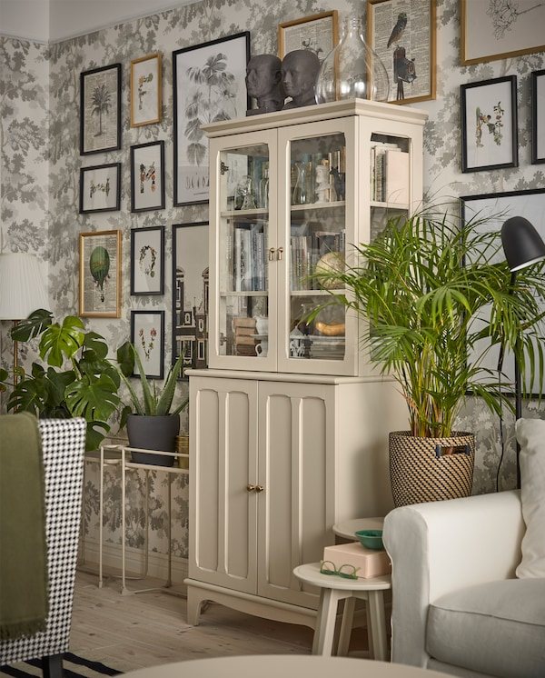 A light beige cabinet with both panel and glass doors stands in front of a wall with leaf-patterned wallpaper.