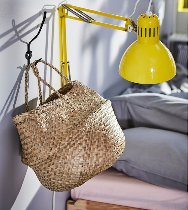 A light beige seaweed basket hung on a wall next to a yellow wall lamp.