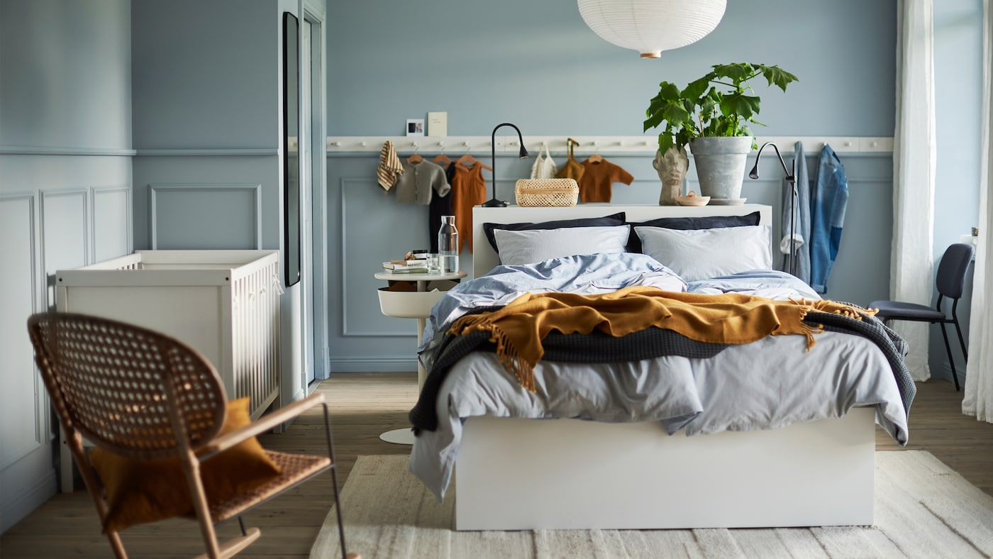 A light blue bedroom with a white bed, a white lamp, a white panel of hooks, a rattan rocking chair and a SUNDVIK baby cot.