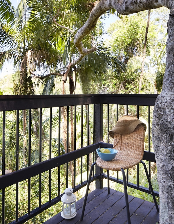 A light blue bowl with fruit on a lightweight rattan chair with black legs standing outside on the tree houses balcony.