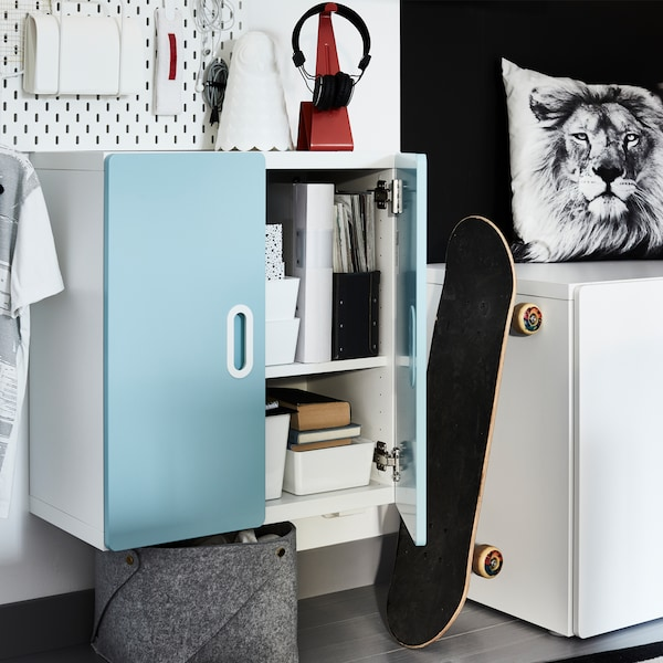 A light blue wall cabinet with organisers inside, a white lamp and a lion-patterned cushion cover.