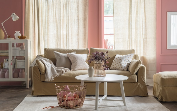 A light brown sofa and footstool in a living room setting with tall windows and pink walls behind.