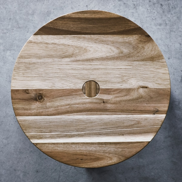 A light brown, wooden, circular piece, laid out on a concrete surface.
