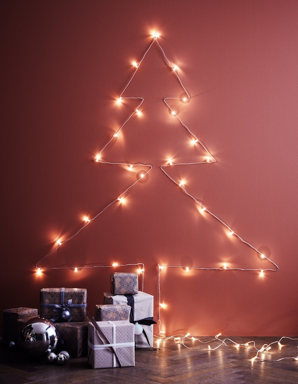 A light chain trailed across a wall in the shape of a Christmas tree, using nails as support and with gifts on the floor.