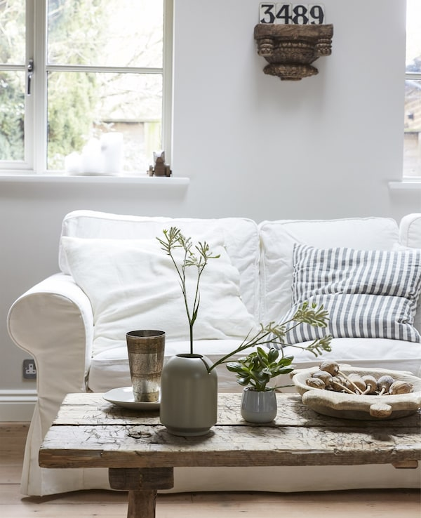 A light-coloured living room with a white sofa and rustic wooden coffee table.
