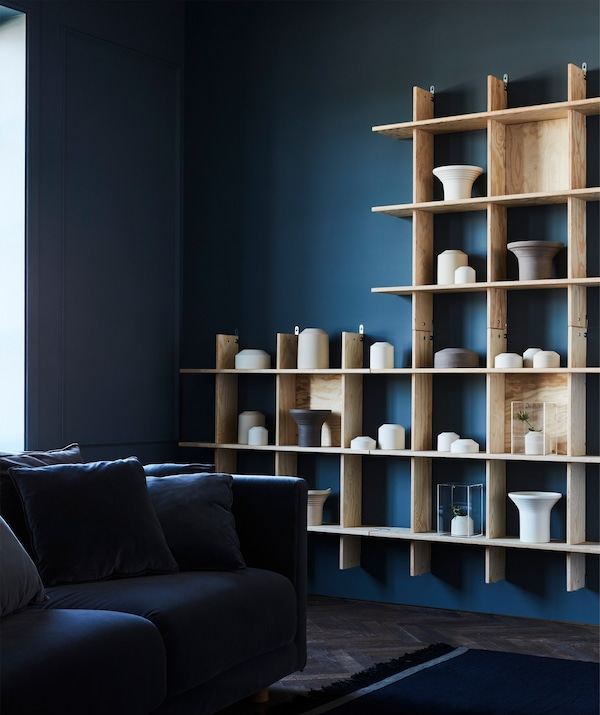 A light-coloured wooden shelving unit filled with ceramic objects contrasting against a dark blue wall in a living room.