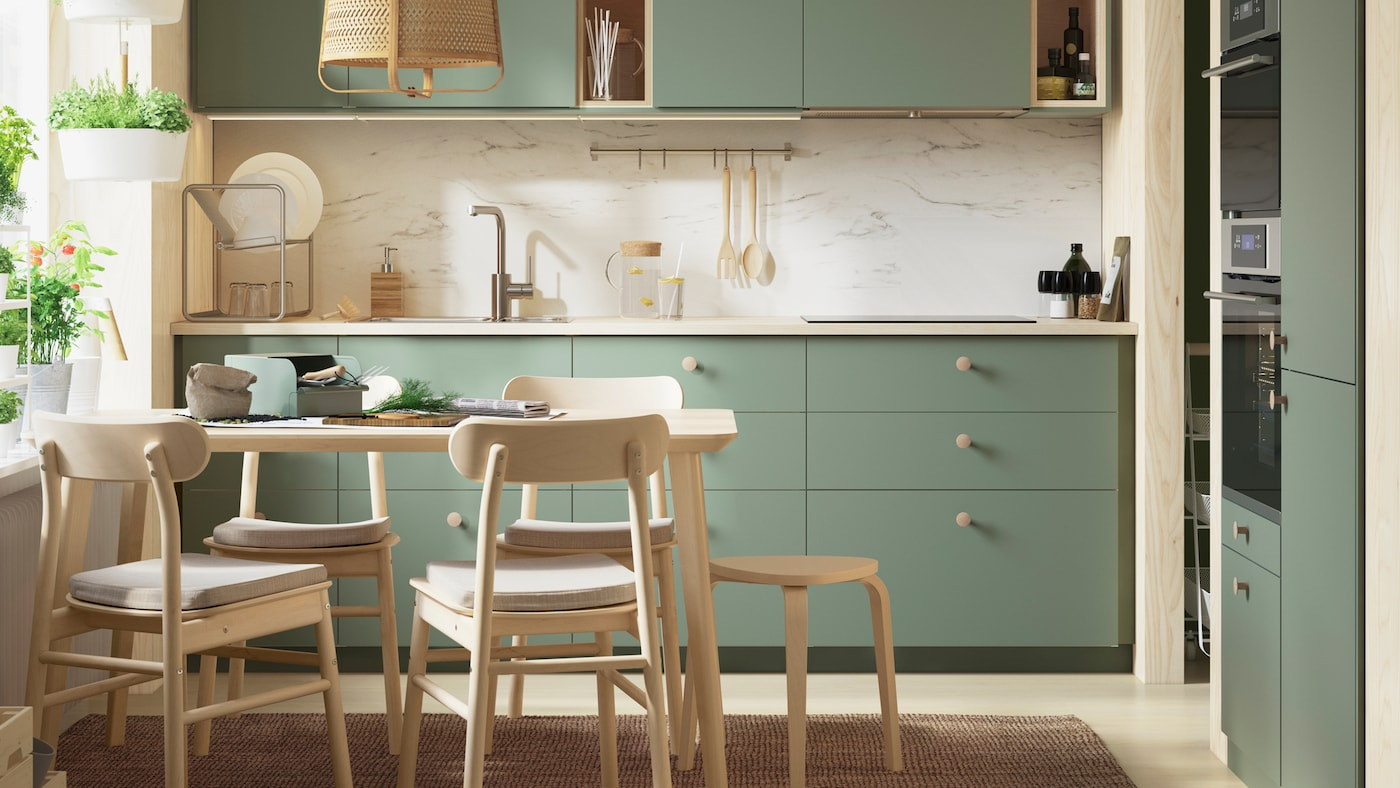 A light-drenched grey-green BODARP kitchen with herbs growing in the window, a table and four RÖNNINGE chairs in birch.