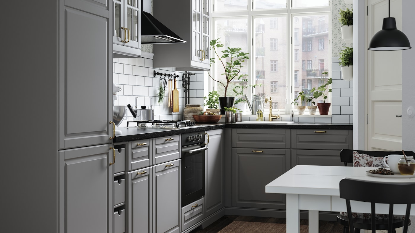 A light-drenched kitchen in traditional style with BODBYN kitchen fronts in grey. There are potted plants on the windowsill.